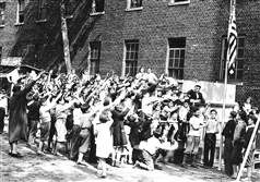 A group of children salutes the flag at the Irene Kaufmann Settlement playground in May 1934.