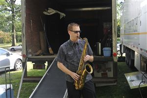 Jason Kush, tenor sax player in the Pittsburgh Jazz Orchestra, warms up behind the stage in Highland Park before the Reservoir of Jazz's first performance.