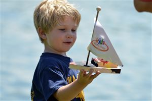 Kyle Meyer, 4, of Toledo, admires the boat he built at the Home Depot Kids workshop during The Regatta at Lake Arthur in Moraine State Park.