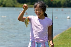 Trina Cheng, 9, of Frederick, Md., admires the little sunfish she caught in Lake Arthur on Sunday afternoon. Fishing was one of the activities offered during The Regatta at Lake Arthur on Sunday afternoon.
