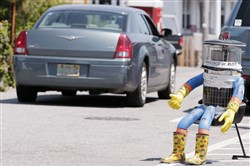 A car drives by HitchBOT, a hitchhiking robot on July 17 in Marblehead, Mass.