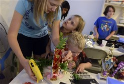 Jodi Buzzard, of Ohio Townhip, works on making a trophy with her children, Rachel, 6, and Simon,4, using found objects supplied by the Pittsburgh Center for Creative Reuse.