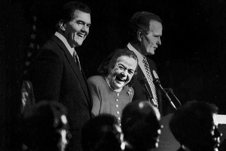 93r00kg6-17 Elsie Hillman reacts as members of the Mendelssohn Choir sing a song to her while she stands on stage with Gov. Tom Ridge, left, and former President George H.W. Bush at the Pittsburgh Hilton and Towers in 1996.