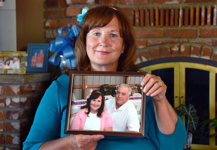 20150805ng-DebbieMills4-3 Debbie Mills of Jefferson Hllls holds a portrait of her husband Jack, who died suddenly. Mrs. Mills talked about what it was like to be faced with funeral planning after an unexpected death.