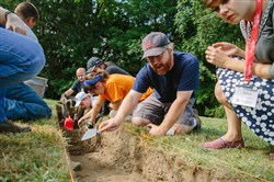 Andrew DuDash, assistant director of the field school at Juniata College, points out areas in the soil during an archaeological dig at Fort Ligonier on Aug. 7.
