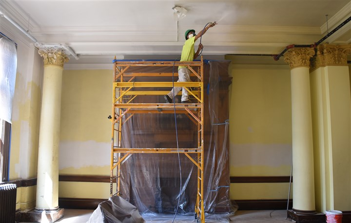 20150817smcarnegie001 James Elish of Patrinos Painting applies primer to the ceiling of the main library room of the Carnegie Free Library and Music Hall in Carnegie. The historic building is in the midst of a $430,000 in repairs and renovations.