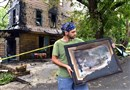 Paul Kuzupas of Scenery Hill carries a heavily damaged print salvaged from the Century Inn, which was struck by fire late Monday night. The print was done by the late, renowned artist Malcolm Parcell, a native of Claysville, Washington County.