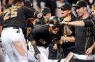 Teammates mob the Pirates' Pedro Florimon after he hit a walk-off single in the 15th inning against the Diamondbacks on Aug. 18.