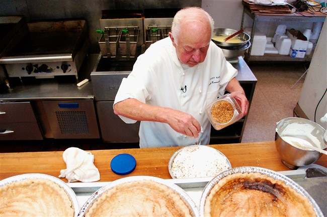 Frank Ruzomberka adds toasted coconut to his Coconut Cream Pie at Grant Bar & Restaurant in Millvale.