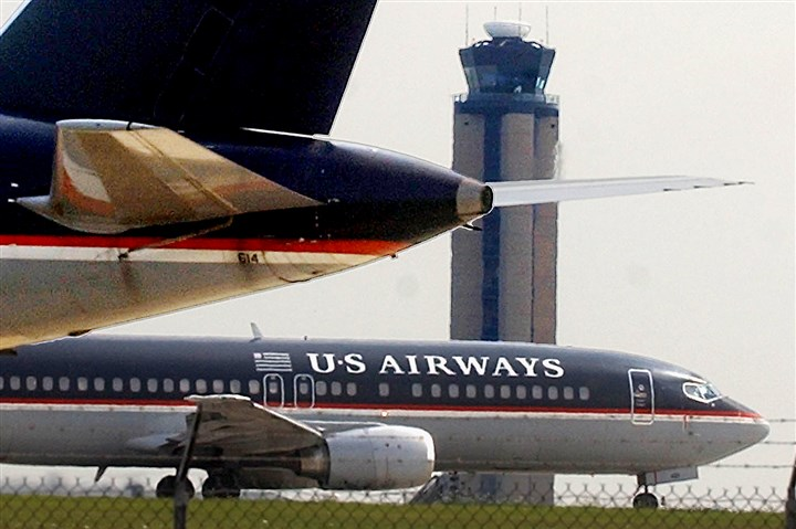 USAIR0821d-18 A jetliner from US Airways taxis past another near the air traffic control tower at Pittsburgh International Airport in 2004.