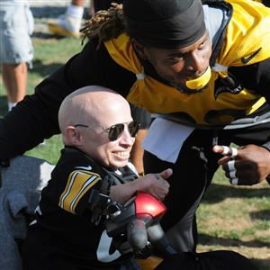 In this 2015 file photo, Verne Troyer left, and former Steeler safety, Shamarko Thomas, right, pose for photos after the Steelers final practice at training camp.