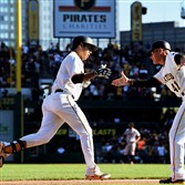 Jung Ho Kang is congratulated by third base coach Rick Sofield after hitting his first of two home runs in a 3-2 victory over the San Francisco Giants at PNC Park in 2015.