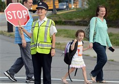 West View Borough crossing guard Debbie Hall shepherds students across busy Perry Highway to West View Elementary on the first day of school in the North Hills School District. She's been a crossing guard for nine years.