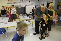 Allen Lucci, 5, shares a moment with his father Ryan Lucci as his mother Mary looks on during kindergarten orientation for families at Carnegie Elementary School in Carnegie on Aug. 19.