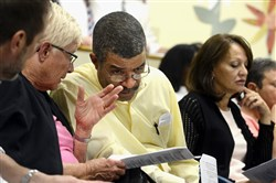 Teacher Barb Leach, left, talks with Mike Evans, Wilkinsburg Education Association president while he waits to speak during a legislative session of the Wilkinsburg School Board on Tuesday.  At far right is teacher Judy Baudoux.