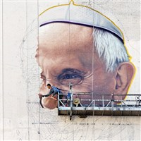 A sign painter outlines the Pope Francis' nose on the side of a New York City office building in preparation for his visit in September.