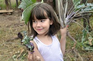 Sawyer Shaw, 8, of Braddock, who was volunteering at Braddock Farms with her father Fitz, shows a kohlrabi for possible saving to farm apprentice Alyssa Kail as she helped clear a bed of plants so the area could be replanted.