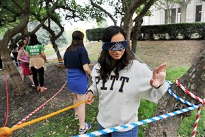 Meghna Datar, 18, of Montgomery, Pa., works her way through the String Maze, an activity meant to teach participants how to ask for help, during the Cathedral Leadership Games for incoming freshmen at the University of Pittsburgh in Oakland.