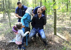 Hungarian policemen detain a Syrian migrant family that entered Hungary on Friday at the border with Serbia, near Roszke. Hungary is nearing completion of a barbed wire border fence to keep out those migrating through the country and authorities plan to send more than 2,000 police officers there.