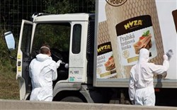 Investigators gather evidence from a truck on the shoulder of a highway south of Vienna, Austria, Thursday. At least 70 migrants, including children, were found dead in the truck, police said.