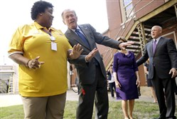Former President George W. Bush dances with band director Asia Muhaimin on Friday as the band plays during a visit to Warren Easton Charter High School in New Orleans.