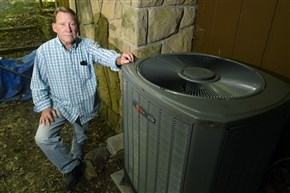 Bob Kramer stands near the heat pump at his Economy home. He recently discovered he'd been in the wrong rate class for electric heating for 14 years, as a previous homeowner had installed a heat pump, and Mr. Kramer filed a formal compliant with the Pennsylvania PUC.