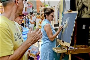 Artist Tonya Butcher of Golden, Va., works on a pastel drawing amid the crowd during the Shadyside Art Festival on Walnut Street.