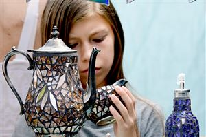 Delaney Rich, 11, of Gibsonia checks out a mosaic teapot set at the booth of artist Michelle Hoff of South Dayton, N.Y., during the Shadyside Art Festival on Walnut Street.