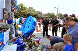 People pay respects at a makeshift memorial Saturday at a gas station in Houston for Harris County Sheriff's Deputy Darren Goforth, who was fatally shot while pumping gas Friday night. Prosecutors on Saturday charged Shannon J. Miles with capital murder in the killing of Deputy Goforth.