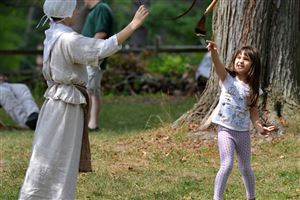 Adele Stamenov, 6, of Bethel Park, tries to throw a corn cob through a hoop held by Lyrick Farley, 13, as they play the game corn darts during the Frontier Frolic and Games day at the Oliver Miller Homestead in South Park.