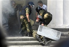 An injured national guard officer is carried away by comrades Monday outside the Parliament building in Kiev, Ukraine. One person was killed and over 100 wounded after an explosive device was thrown during a protest.