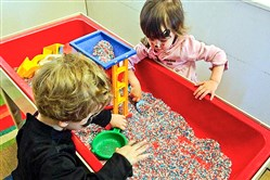 Elliott Lee, left, and Marley Mills, both 2, enjoy sensory play at the Seesaw Center's rice table.