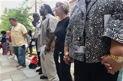 People gather hand-in-hand in prayer Monday outside the Trinity Episcopal Cathedral, Downtown, to mark Overdose Awareness Day.