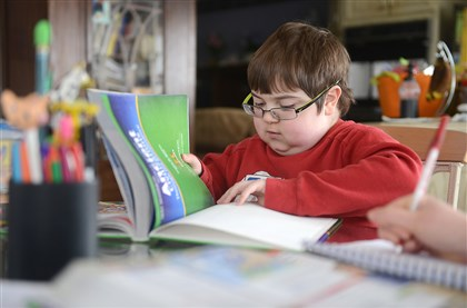 Billy Ellsworth works on social studies lessons at home in Coraopolis. He is part of a clinical trial for eteplirsen, a drug that has not only slowed the progession of Duchenne muscular dystrophy, but improved his symptoms.