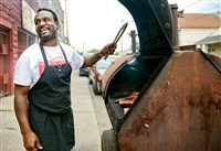 "Dave Jenkins, 49, ""pit master,"" owner and operator at The Dream Bar-B-Q, cooks in front of his restaurant on North Braddock Avenue."