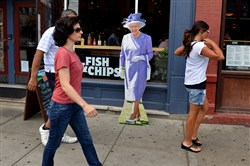 People walk past a card board cut out of Queen Elizabeth while she stands on the South Side.