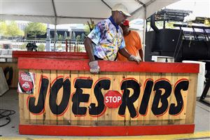 Joe Jackson of Columbus, Ohio, moves one of his signs for his stand on the North Shore outside Heinz Field in preparation for the Kickoff and Rib Festival this weekend.