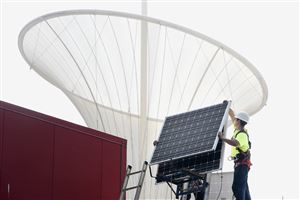"Matt Bovee of Munhall lifts one of 36 solar panels being installed on the roof of the Highmark Sports Works on the North Shore, with the ""E-Motion"" weather cone of the Carnegie Science Center in the background. Mr. Bowee works for Energy Independent Solutions."