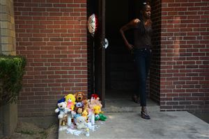 A resident walks past a memorial site outside the apartment at Allegheny Commons on the North Side where 22-months-old Josiah Taylor was shot to death.