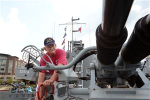 Bob Chick of Peoria, Ill., cranks up the barrels of a 40-mm gun aboard the USS LST 325 docked along the Allegheny River.