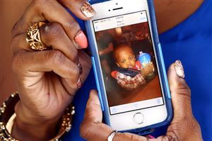 Shaniqua Taylor, 26, holds up a photo of her son Josiah Taylor outside the home of her pastor in Munhall on Wednesday. Josiah, 22-months-old, was shot and killed Tuesday at the Allegheny Dwellings on the North Side. Police have charged Ms. Taylor's boyfriend Harrison Marshman Jr., 30, in the death.