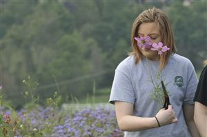 Lilly Fuller, 16, inhales the fragrance of one of the flowers she cut at Simmons Farm in McMurray while on an outing with her mother and sister.