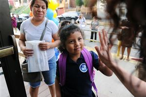 Ana Galindo looks on as her daughter, Lizet Garcia, 5, gets a high-five from volunteers on the first day of school at Pittsburgh Arsenal PreK-5 in Lawrenceville.