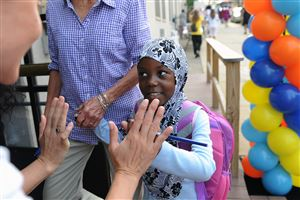 Aba Awad, 5, of Northview Heights gets a high-five from volunteers on the first day of school at Pittsburgh Arsenal PreK-5 in Lawrenceville.