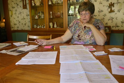 Milly Scott sits in her Ben Avon Heights home Monday with a table full of paperwork regarding the cost of her prescriptions.