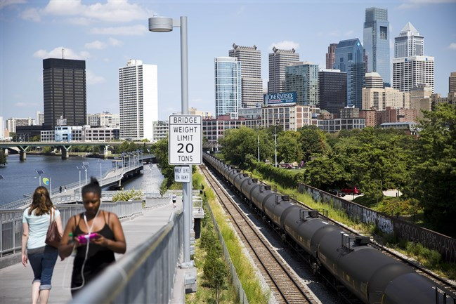 Pedestrians walk past train tank cars, with signs indicating petroleum crude oil, standing idle on the tracks in Philadelphia. While railroads have long carried hazardous materials through congested urban areas, cities are now scrambling to formulate emergency plans and to train firefighters amid the latest safety threat: a fifty-fold increase in crude shipments that critics say has put millions of people living or working near the tracks at heightened risk of derailment, fire and explosion.