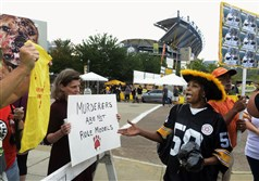 Steffi Bruinghaus of Squirrel Hill, left, protests against Michael Vick, as Renarda Walker, right, supports him during a rally Thursday outside Heinz Field as the Steelers played the Carolina Panthers in a preseason game. More than 100 people demonstrated against the new backup Steelers quarterback who served jail time for dogfighting.