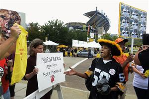 Steffi Bruinghaus of Squirrel Hill, left, protests against Steelers quarterback Michael Vick because of his dogfighting conviction as Renarda Walker and Michael Scarver, right, of Mars say he should be forgiven.