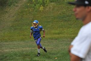 Drew Lopez, 12, sprints during warm-ups as his father Milton Lopez looks on at Cornell High School.
