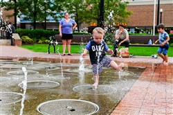 Children play in the water fountain at SouthSide Works.